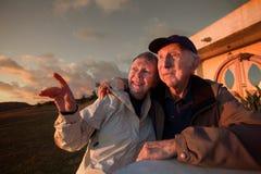 Glückliche Paare, die draußen sitzen lizenzfreie stockfotografie
