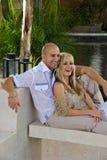 Glückliche Paare, die durch das Pool lounging sind Lizenzfreie Stockbilder