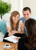 Glückliche Paare, die einen Vertrag unterzeichnen Lizenzfreie Stockbilder