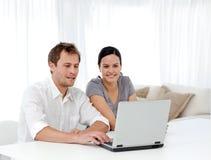 Glückliche Paare, die etwas auf dem Laptop betrachten Stockbild