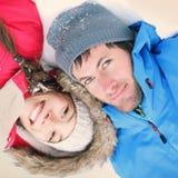 Glückliche Paare, die im Schnee liegen Stockfoto