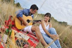 Glückliche Paare, die Landschaftpicknick genießen Lizenzfreie Stockfotos