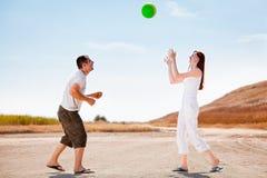 Glückliche Paare, die mit einer Kugel spielen Stockbild