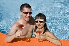 Glückliche Paare, die mit rosafarbenem Martini in einem Pool rösten Stockfotos