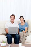Glückliche Paare, die online mit ihrer Kreditkarte kaufen Stockfotografie
