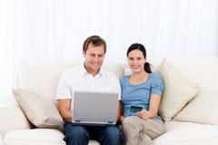 Glückliche Paare, die online mit Laptop und Cd kaufen stockbild