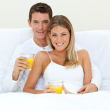 Glückliche Paare, die Orangensaft auf ihrem Bett trinken Lizenzfreie Stockfotografie