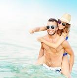 Glückliche Paare, die Spaß am Strand haben Lizenzfreies Stockbild