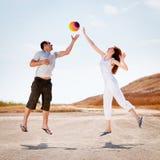 Glückliche Paare, die springen, um eine Kugel abzufangen Lizenzfreie Stockbilder