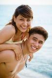 Glückliche Paare durch den Strand Lizenzfreie Stockfotos