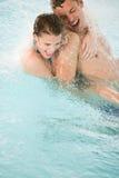 Glückliche Paare haben Spaß unter Wasserstrom im Pool Stockfoto