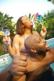 Glückliche Paare im Pool Stockfotos