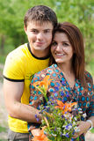 Glückliche Paare mit Blumen u. der Fahrradaufstellung Stockbild
