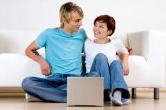 Glückliche Paare mit Computer Stockfotos