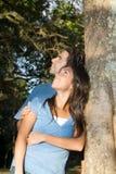 Glückliche Paare starren oben in die Bäume an. Vertikal Stockbild