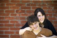 Glückliche Paare und Backsteinmauer Stockfoto
