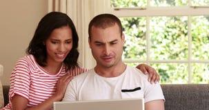 Glückliche Paare unter Verwendung des Laptops stock video footage