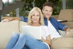 Glückliche Paare unter Verwendung des Laptops Stockbilder