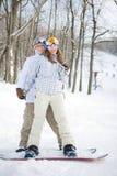 Glückliche Paare von Snowboarders stockfotos