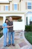 Glückliche Paare zu Hause mit Zeichen Lizenzfreie Stockbilder