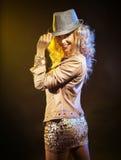 Glückliche partying Frau, die einen Hut berührt Lizenzfreie Stockbilder