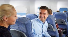 Glückliche Passagiere, die im Flugzeug sprechen stockbild