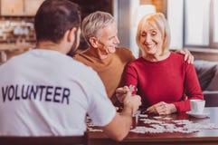 Glückliche Pensionäre, die Puzzlespiele zusammenfügen lizenzfreies stockfoto