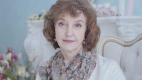 Glückliche positive elegante reife Dame, die im Lehnsessel oben schaut im Kameraabschluß sitzt Blumen im Hintergrund stock video
