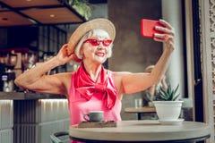 Glückliche positive Frau, die ein selfie an ihrem Telefon nimmt stockbilder