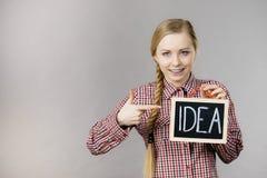 Glückliche positive Frau, die Ideenzeichen hält Stockfotos