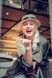 Glückliche positive Frau, die viele Luftküsse sendet stockfoto
