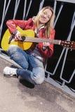 Glückliche positive kaukasische blonde Frau, die in der roten Lederjacke und in den Jeans mit Gitarre Outdors aufwirft Stockbild
