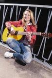 Glückliche positive kaukasische blonde Frau, die draußen in der roten Lederjacke und in den Jeans mit Gitarre auf dunkler Straße  Stockfoto