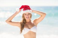 Glückliche recht blonde schauende Kamera mit Weihnachtsmann-Hut Stockbild
