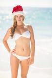 Glückliche recht blonde schauende Kamera mit Weihnachtsmann-Hut Lizenzfreies Stockfoto