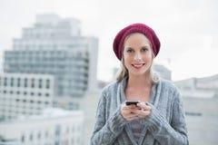 Glückliche recht blonde Versenden von SMS-Nachrichten draußen Stockbilder