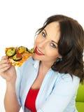 Glückliche recht junge Frau, die eine Scheibe der frisch gebackenen vegetarischen Pizza isst Stockfotos