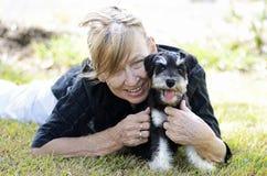 Glückliche reife ältere Frau, die Haustierhündchen umarmend lächelt lizenzfreie stockbilder