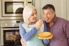 Glückliche reife blonde Fütterungstorte zum Ehemann Lizenzfreie Stockbilder