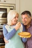 Glückliche reife blonde Fütterungstorte zum Ehemann Stockbilder