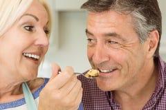 Glückliche reife blonde Fütterungstorte zum Ehemann Lizenzfreies Stockfoto