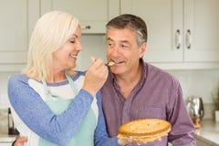Glückliche reife blonde Fütterungstorte zum Ehemann Stockfotografie