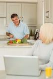 Glückliche reife Blondine, die den Laptop spricht mit Ehemann verwendet Lizenzfreie Stockfotografie