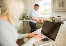 Glückliche reife Blondine, die den Laptop spricht mit Ehemann verwendet Stockbild