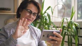 Glückliche reife Frau in den Gläsern lächelnd und wellenartig bewegend stock footage