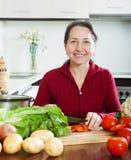 Glückliche reife Frau, die das geliehene Diätmittagessen kocht Stockfotografie
