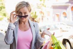 Glückliche reife Frau, die an der Kamera mit ihren Einkaufskäufen lächelt Stockbild