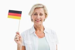 Glückliche reife Frau, die deutsche Flagge hält Stockfotos