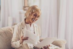Glückliche reife Frau, die Dokumente überprüft lizenzfreie stockfotografie
