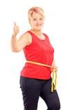 Glückliche reife Frau, die ihre Taille nach Diät misst und thum gibt Stockbilder